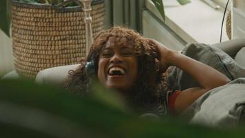 vrouw met koptelefoon liggend op haar rug zingend glimlachend en bewegend video