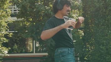 hombre con auriculares sonríe camina y baila en la acera video