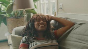 vrouw met koptelefoon liggend op de bank met gesloten ogen en bewegend hoofd video