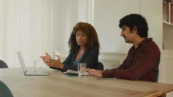 vrouw en man praten aan tafel met laptop en notebook video