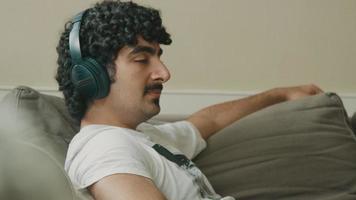 un homme avec un casque assis sur un canapé bouge la tête en bâillant en rythme video