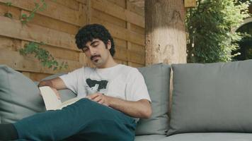 El hombre en el sofá en el jardín lee y convierte el libro video