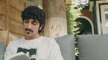 El hombre en el sofá en el jardín lee el libro pasa la página y mira video