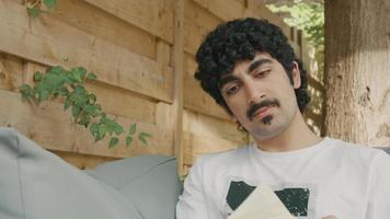 El hombre en el sofá en el jardín lee un libro y pasa las páginas video