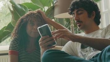 vrouw en man op bank praten over smartphone vastgehouden door man video
