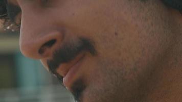 man met koptelefoon zittend in de zon met bewegend hoofd en glimlachend video