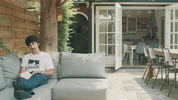 l'homme sur le canapé sur la terrasse lit un livre et tourne la page video