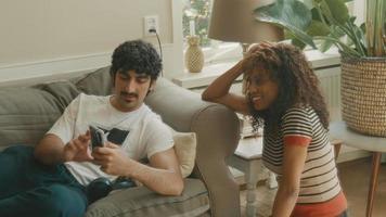 man op de bank en vrouw naast hem praten over smartphone video
