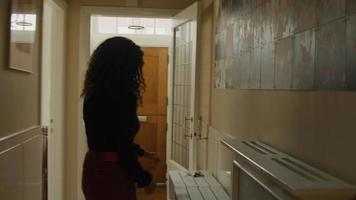 kvinna går till ytterdörren och hämtar nycklar och löv video