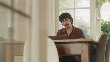 Man sitting at table watching screen laptop video