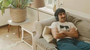 L'homme avec un casque allongé sur un canapé bouge la tête sur le rythme à la recherche de plaisir video