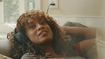 vrouw met koptelefoon liggend op haar rug op de bank praten en zingen video