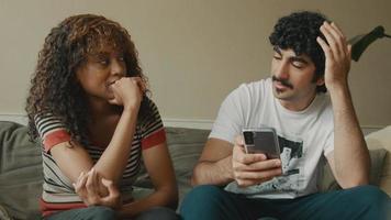 vrouw en man op bank praten terwijl man smartphone vasthoudt video