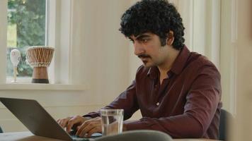 hombre sentado a la mesa escribiendo en la computadora portátil video