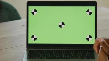 Close up of laptop with green screen on table and two people in front video