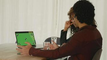 Woman and man at table having conversation with green screen laptop video
