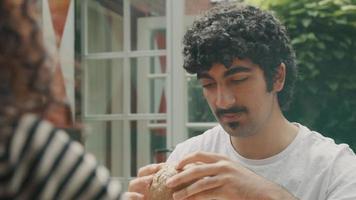 man aan tafel in de tuin praat met vrouw terwijl hij naar een broodje kijkt video