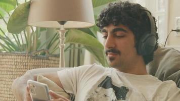 un homme avec un casque assis sur un canapé bouge la tête au rythme video