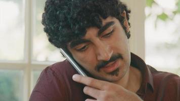 homme travaillant sur ordinateur portable et parlant sur smartphone video