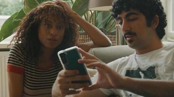 kvinna och man i soffan talar om smartphone som hålls av mannen video