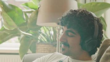 l'homme avec un casque assis sur un canapé bouge la tête sur le rythme et sourit video