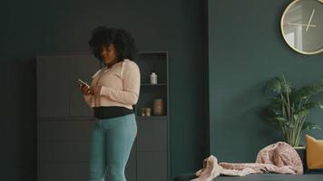 kvinna med hörlurar och smartphone dansar i vardagsrummet video