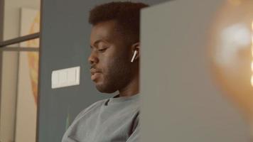 man met koptelefoon zit bewegend hoofd en kijkt naar smartphone video