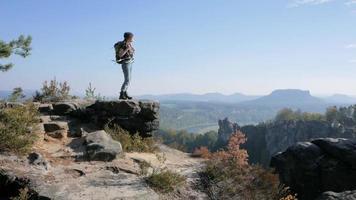 jeune femme voyageur avec sac à dos debout sur la falaise dans les montagnes video