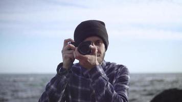 junger männlicher Reisender mit Fotokamera am Strand video