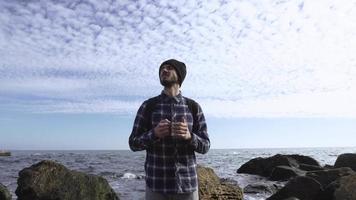 männlicher Reisender trinkt Kaffee am Strand video