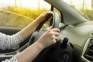 Manos de una mujer en el volante de un automóvil en movimiento al atardecer foto