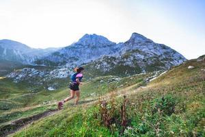Mujer de montaña deportiva paseos en sendero durante el entrenamiento de resistencia foto
