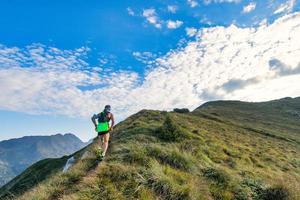 Hombre de montaña deportivo cabalga en sendero durante la carrera de resistencia foto