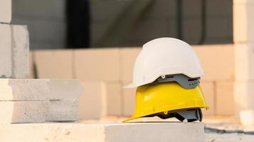 casco en el fondo de la construcción del sitio, seguridad del casco, día del trabajo foto