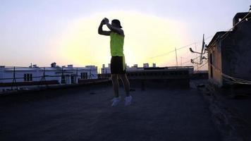 Young male boxer or karate fighter training on the roof video