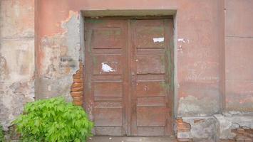 Imagen de fondo de la hoja de la planta de la puerta de madera de la pared de ladrillo de hormigón roto viejo foto