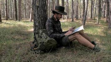 jeune homme randonneur, assis dans la forêt de pins avec carte en mains video