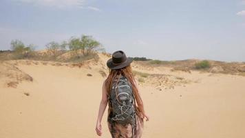Randonneur de jeune femme voyageant seul avec sac à dos dans le désert video
