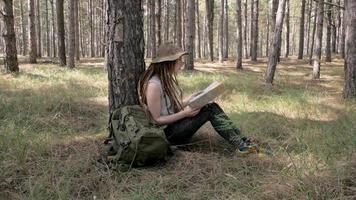 jeune femme voyageur dans la forêt avec carte en mains video