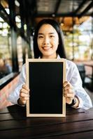 smile woman holding black board in cafe photo