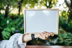 hand woman holding white board in the garden photo