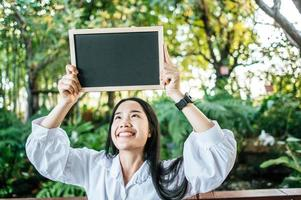 hand woman holding black board in the garden photo
