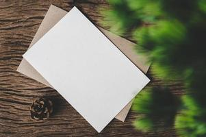 A blank card is placed on envelope and leaf with wood background photo