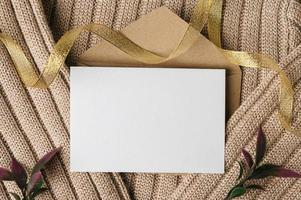 A blank card is placed on envelope and a sweater photo
