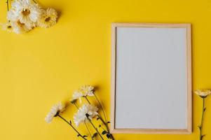 White board with envelope and flower is placed on yellow background photo