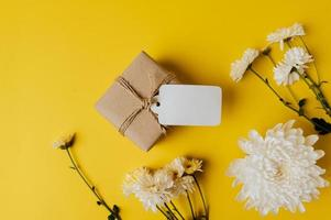 gift box with blank tag and flowers is placed on yellow background photo