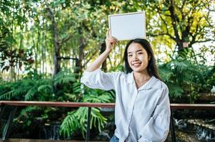 smile woman holding white board in the garden photo