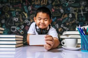Child acting with blank card in the classroom photo