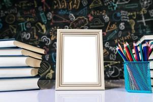 marco de fotos blanco, libro y lápices de colores en el aula