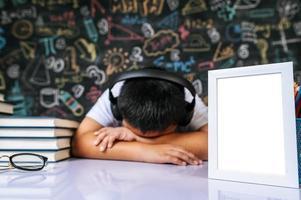niño sentado y durmiendo con marco de fotos en el aula
